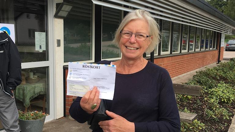En kvinna står utanför en vallokal och håller upp ett röstkort.
