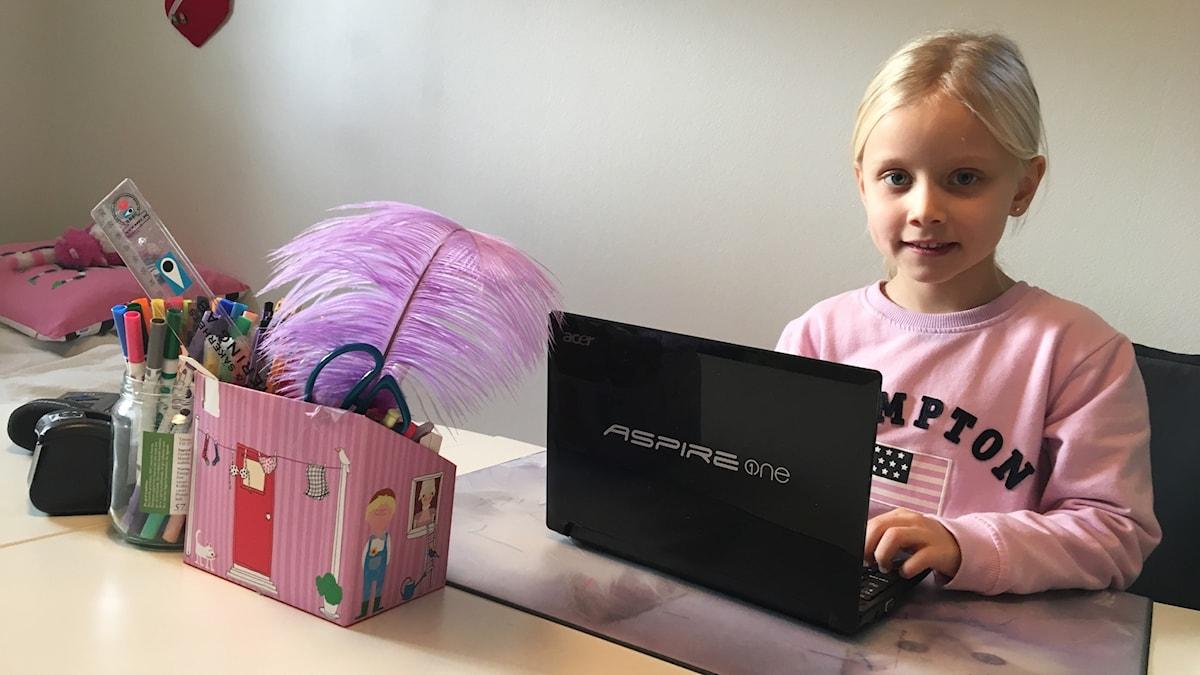 Signe Hederås sitter vid sin dator bakom sitt skrivbord.