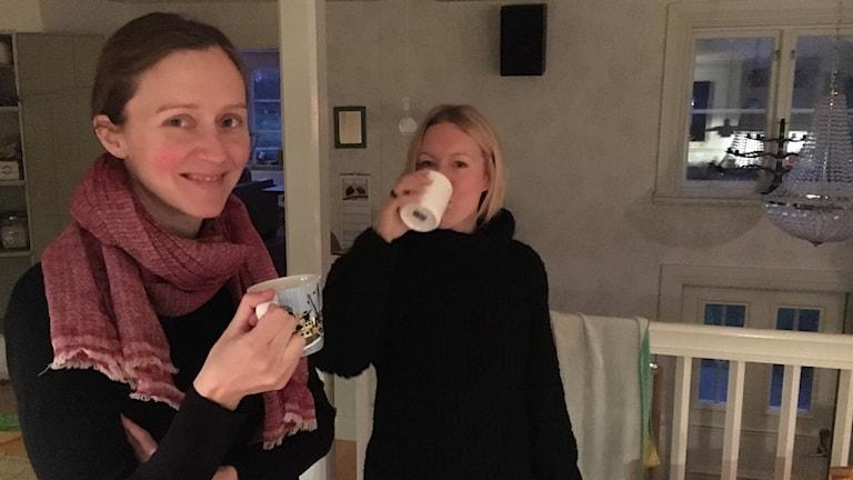 Karin Wedin och Agneta Carlsson står i ett kök och dricker kaffe.