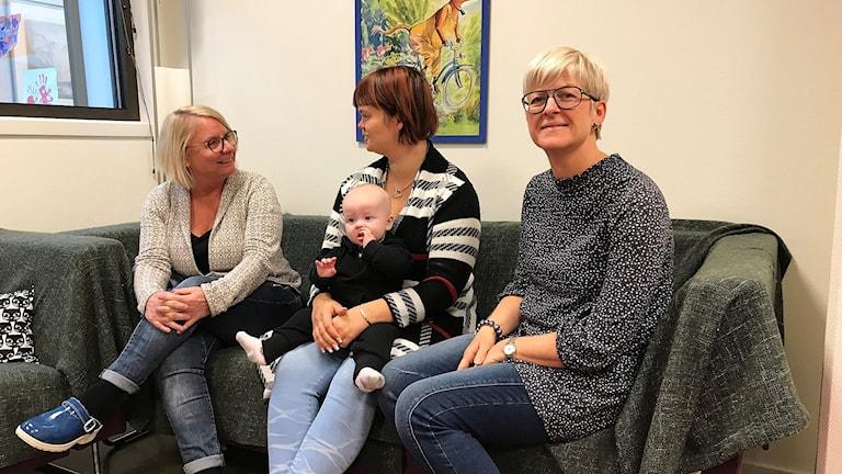 Tre kvinnor sitter i en soffa, en har ett barn i knät