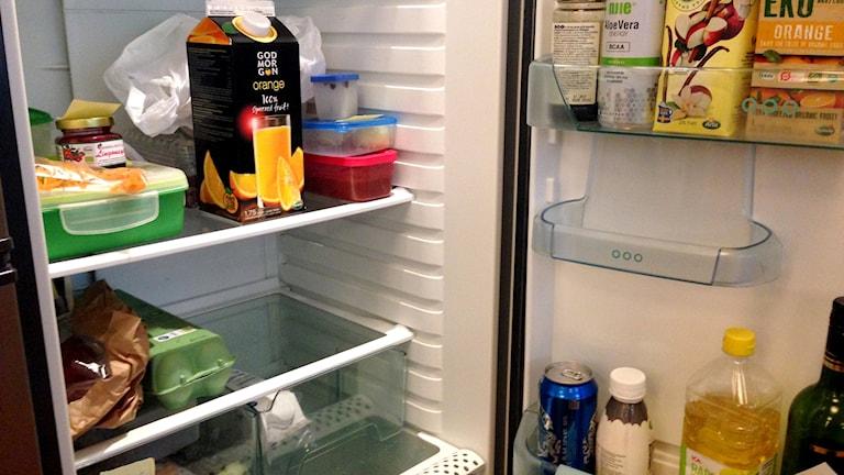 Ett kylskåp med juice, en äggkartong och olja etc.