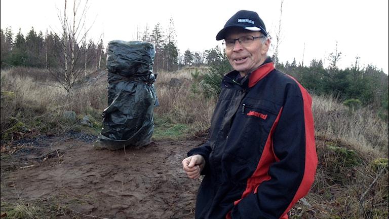Göte Carlsson framför stenen som inte avtäckts ännu. Foto: Per Brolléus/Sveriges Radio
