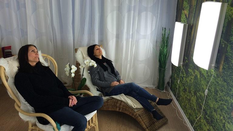 Bettina Widén och Sofie Gockert njuter av ljusterapin. Foto: Carina Bergqvist/Sveriges Radio