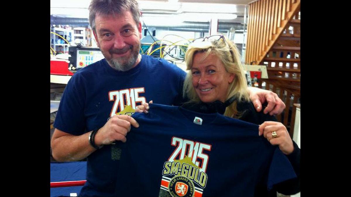 Tony Karlsson vid tryckeriet håller upp en tröja för P4:s reporter Carina Bergqvist.