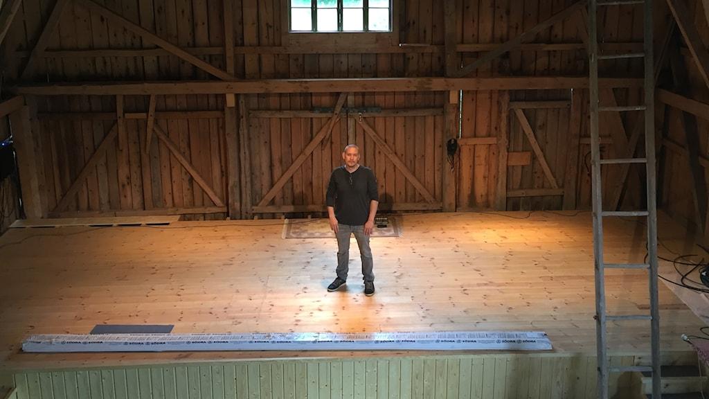 Tonsättaren Tobias Broström står ensam i mitten av konsertscenen i ladan Tagaborg.