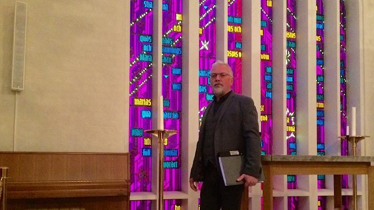 Mats Lindblad från Växjö pastorat framför korfönstret i domkyrkan som håller på att vittra sönder. Foto: Lena Gustavsson/Sveriges Radio