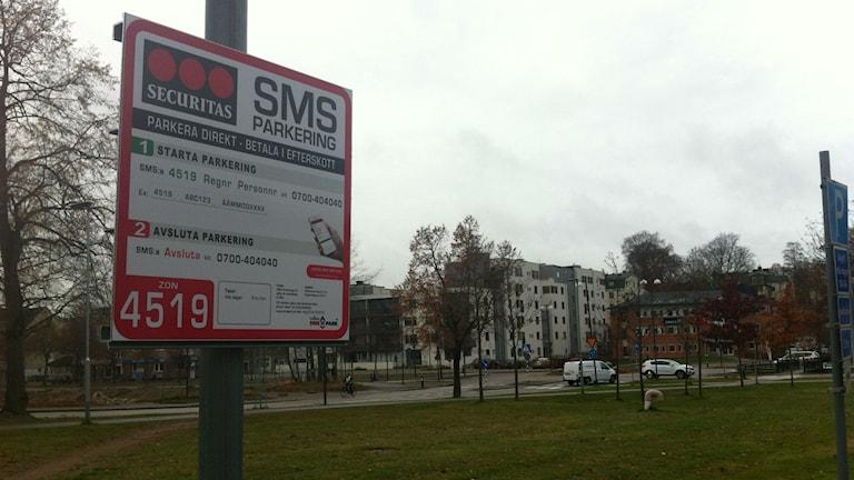 här ser man en skylt vid en parkering där det står att man ska sms:a för att få en biljett.