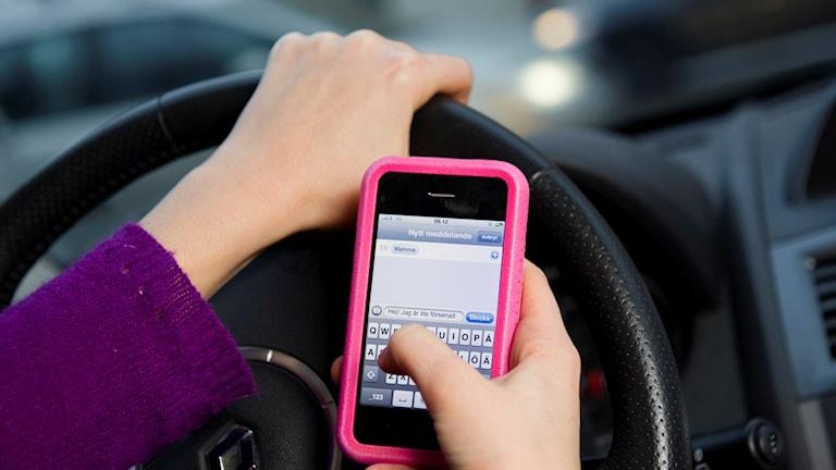 En person kollar mobilen samtidigt som hen kör.