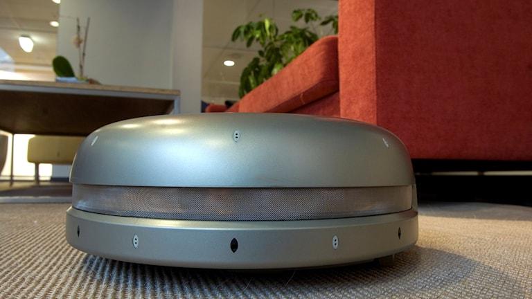 En robotdammsugare på ett golv vid en soffa.