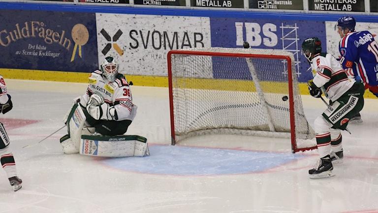 Några hockeyspelare framför mål.