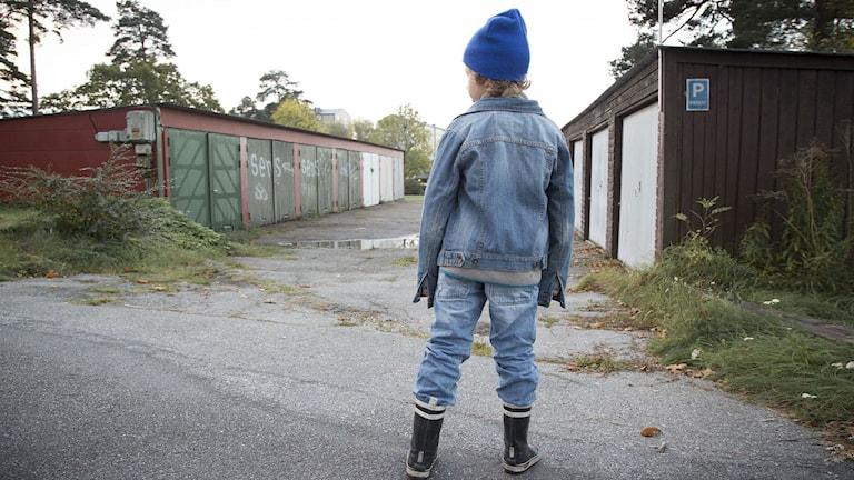 Ett barn står med ryggen till.