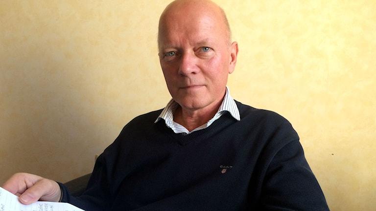 Jan Petersson sitter framför en gul vägg med ett papper i handen.