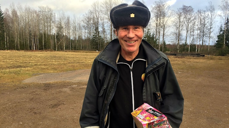 Jonas Grahn står utomhus och håller i en fyrverkeri-tårta