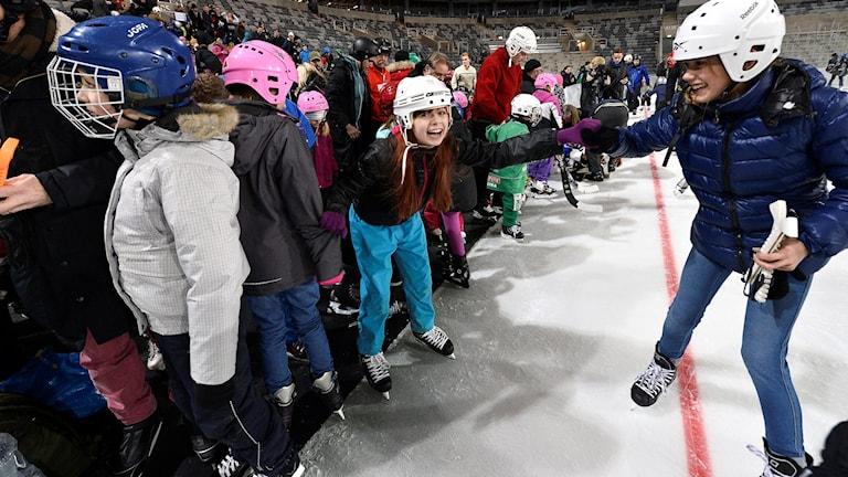 Barn på skridskor i hockeyrinken.