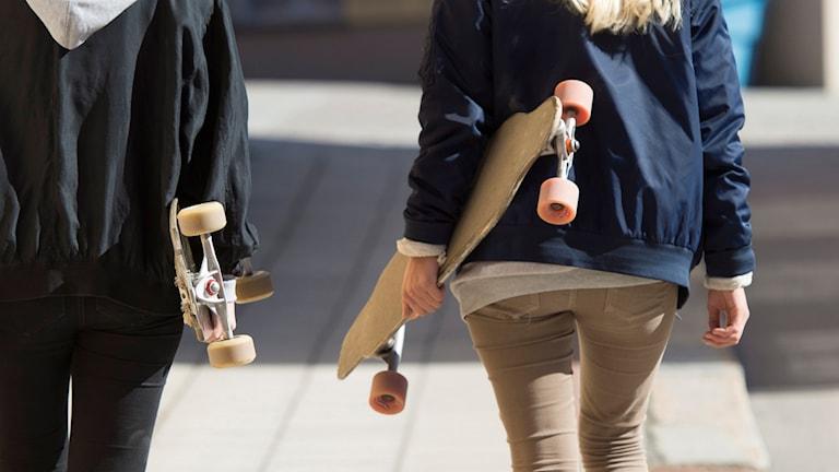 Två personer går med varsin skateboard.