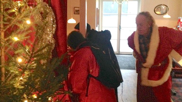 Tomten tittar på besökare som ska ha julklapp.