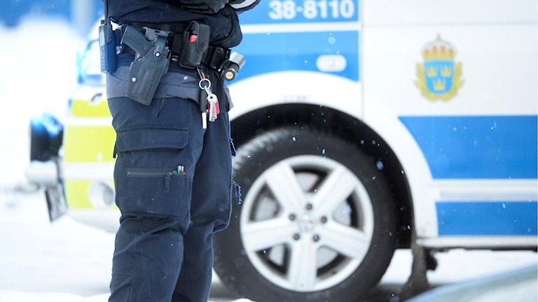 En polis står utanför en polisbil.