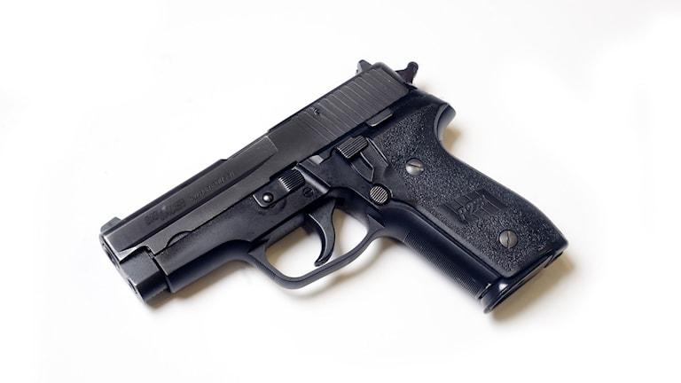 En bild på en pistol som ligger på en plan yta.
