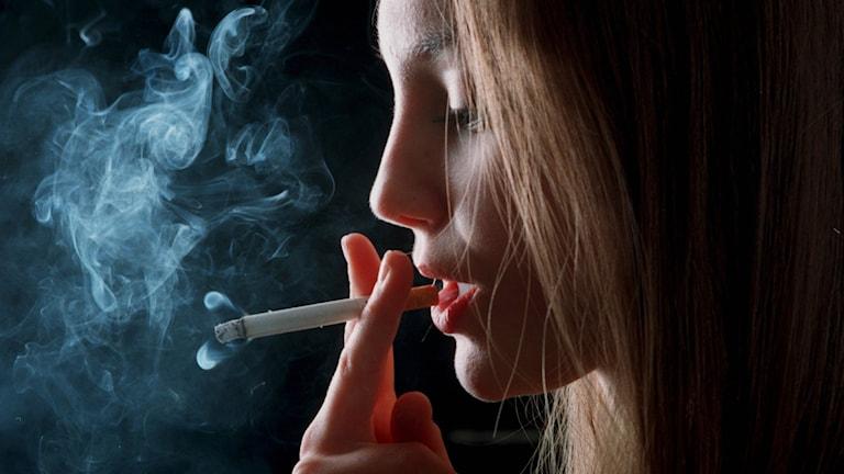 Ung kvinna röker.