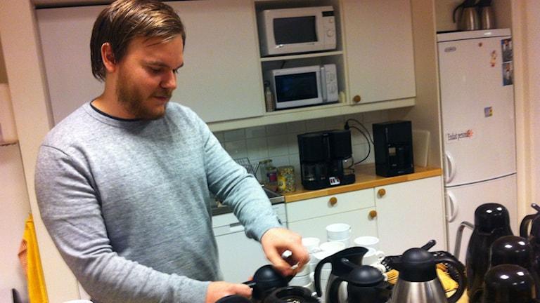 Här ser man Viktor Lundin som förbereder fika till läxhjälpen för nyanlända. Foto: Anneli Koskinen/Sveriges Radio