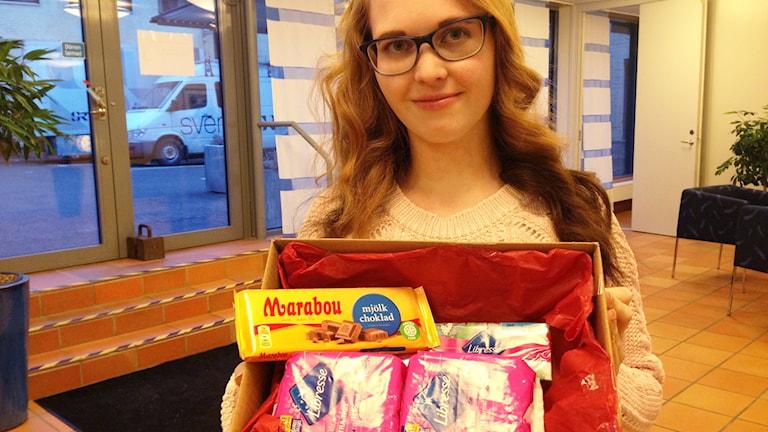 Annie Johansson håller upp en låda med mensskydd och choklad.