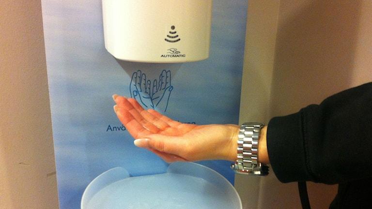 Här ser man en hand som får handsprit från en maskin.