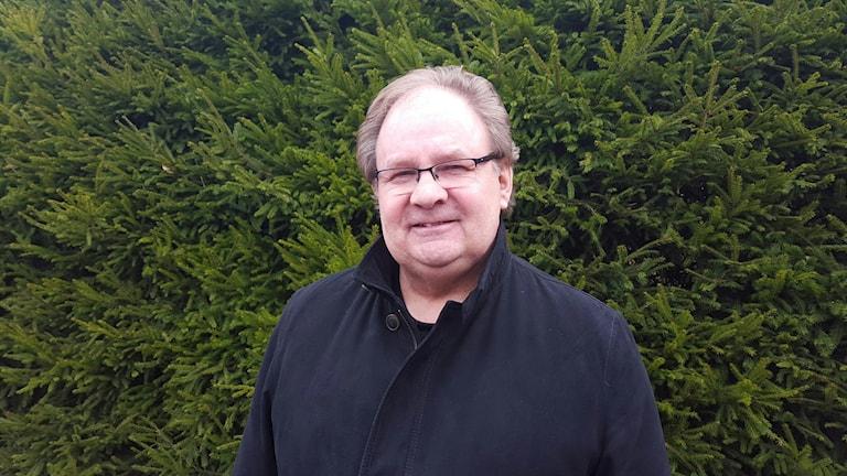 Thomas Klüft står framför en stor grön buske