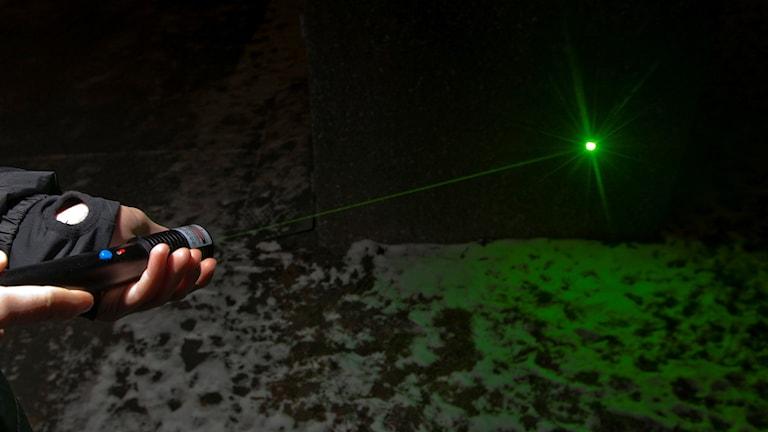 En hand visar upp grön laser