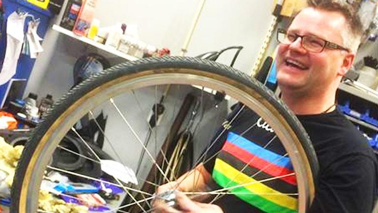 Palle Johansson skrattar med ett cykeldäck.