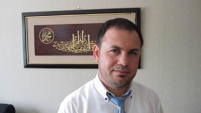 Himan Hassan står framför en tavla.