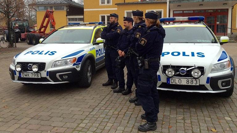 Poliser vid polisbilar.