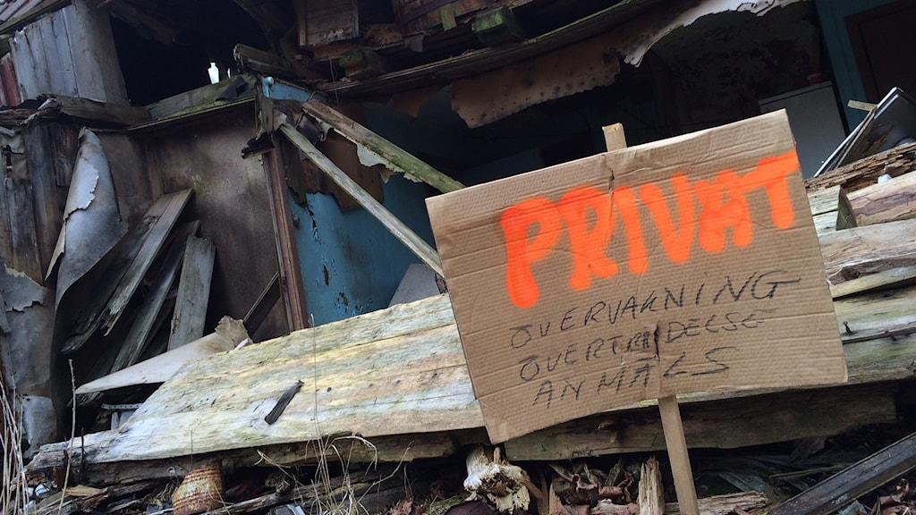 Privat skylt vid övergivet hus webb