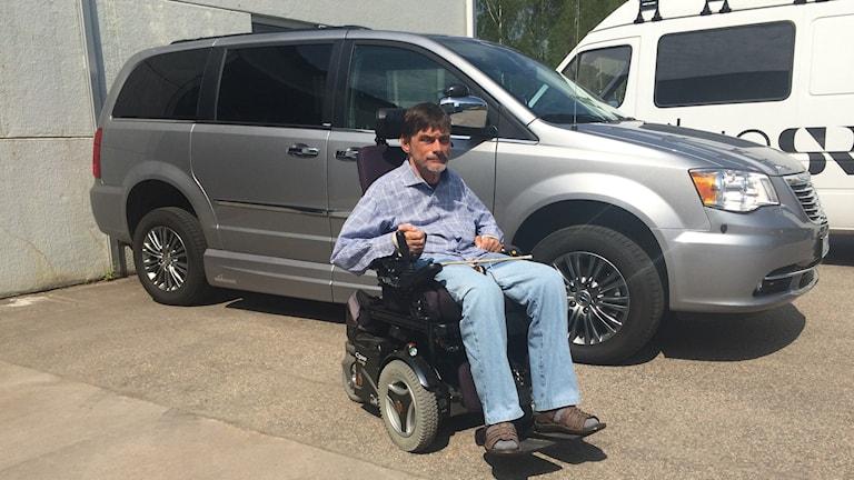 Lutte sitter i sin rullstol bredvid sin bil på bild.