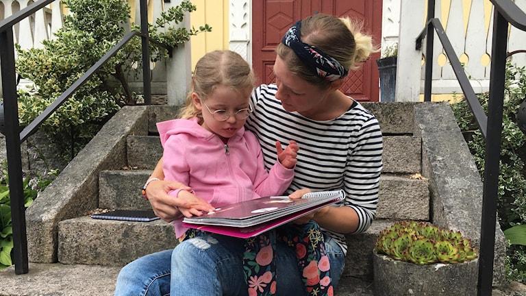 femåriga Alice sitter i mamma Emelies knä på yttertrappen och kollar i en barnbok.