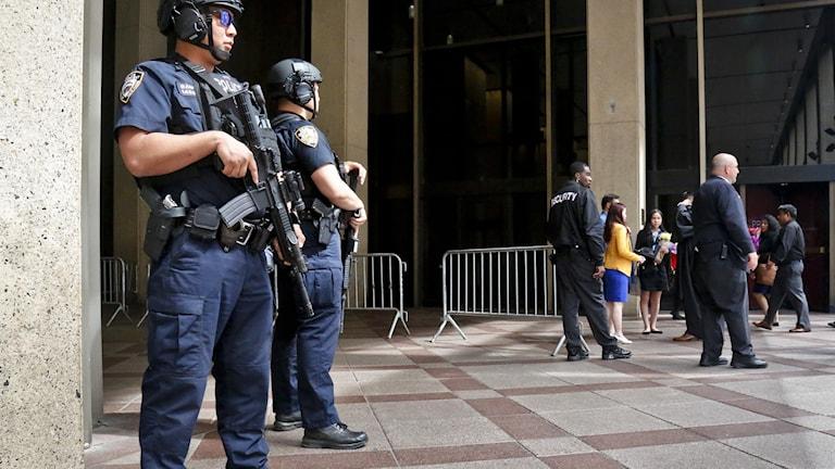 Poliser i new york står och vaktar en byggnad.