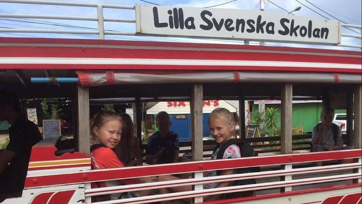 Barnen Erlandsson sitter i en buss som det står Lilla svenska skolan på och tittar mot kameran.