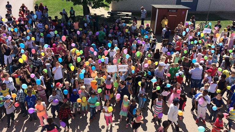 Eleverna står på Grönkullaskolans skolgård med ballonger i händerna.