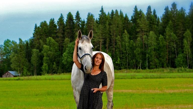 Ulrika Fåhreus med hästen Bacchara står i en hage.