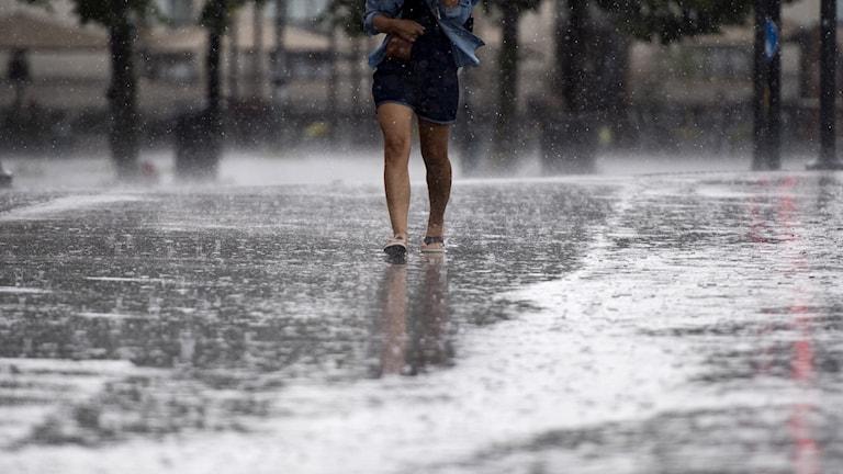 Kvinna går i vattenpöl.