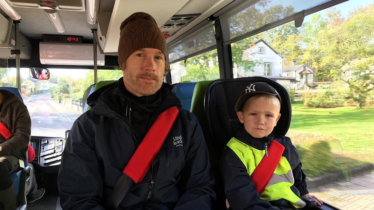 En förskolepedagog och ett barn sitter i bussen och tittar in i kameran.