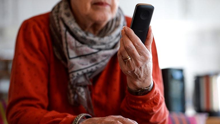 Äldre kvinna håller i en mobiltelefon