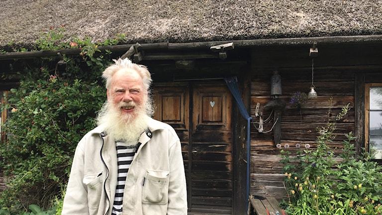 En man med långt vitt skägg står utanför ett gammalt trähus.