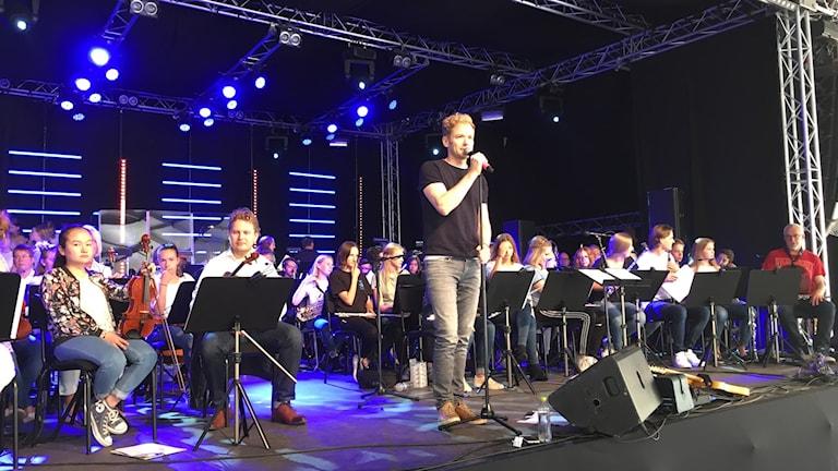 En man står och sjunger i en mikrofon på en scen. Runt omkring sitter ungdomar med olika instrument.
