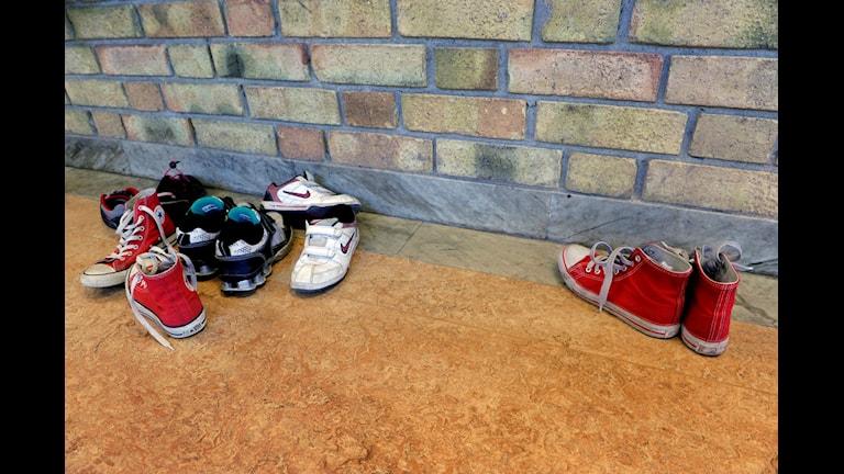 Skolkorridor med skor utanför ett klassrum, ett par står vid sidan om.