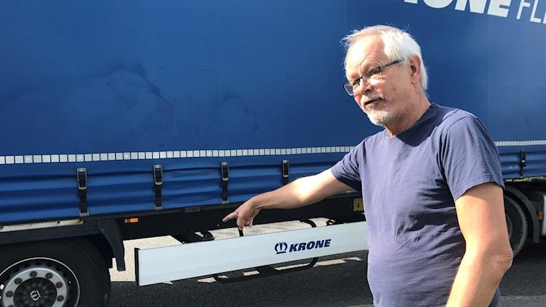 Lars  Andersson pekar på en blå lastbil