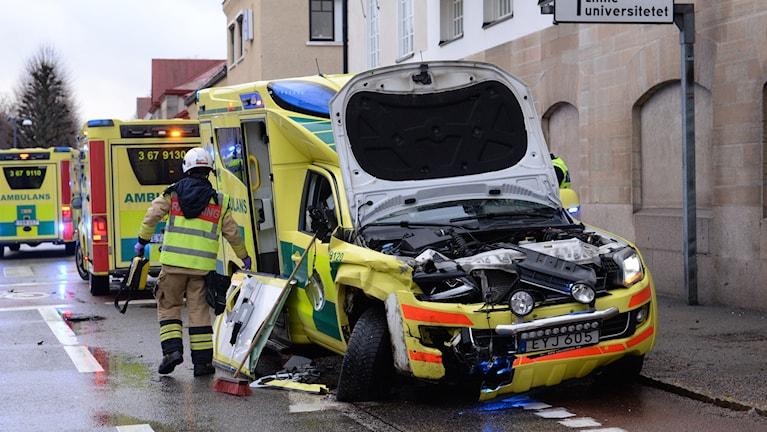 Ambulans med demolerad front. Flera utryckningsfordon och en brandman som tar undan bråte från vägen.