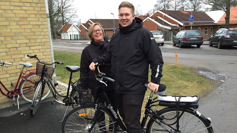 Britt-Marie Tornfalk och Gustav Persson, hemtjänsten Älmhult står utomhus vid en av deras cyklar.