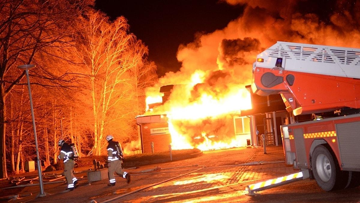 Övertänd skolbyggnad i Sandsbro. Brandbild och brandmän.