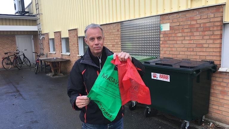 I handen håller Conny en röd och en grön påse.