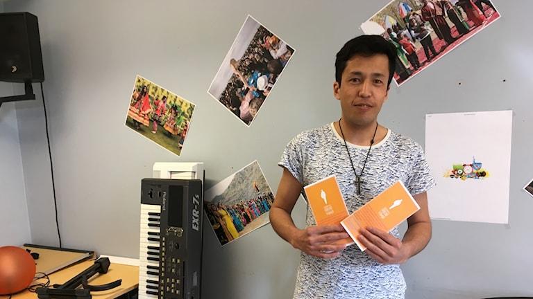 En man håller upp två broschyer